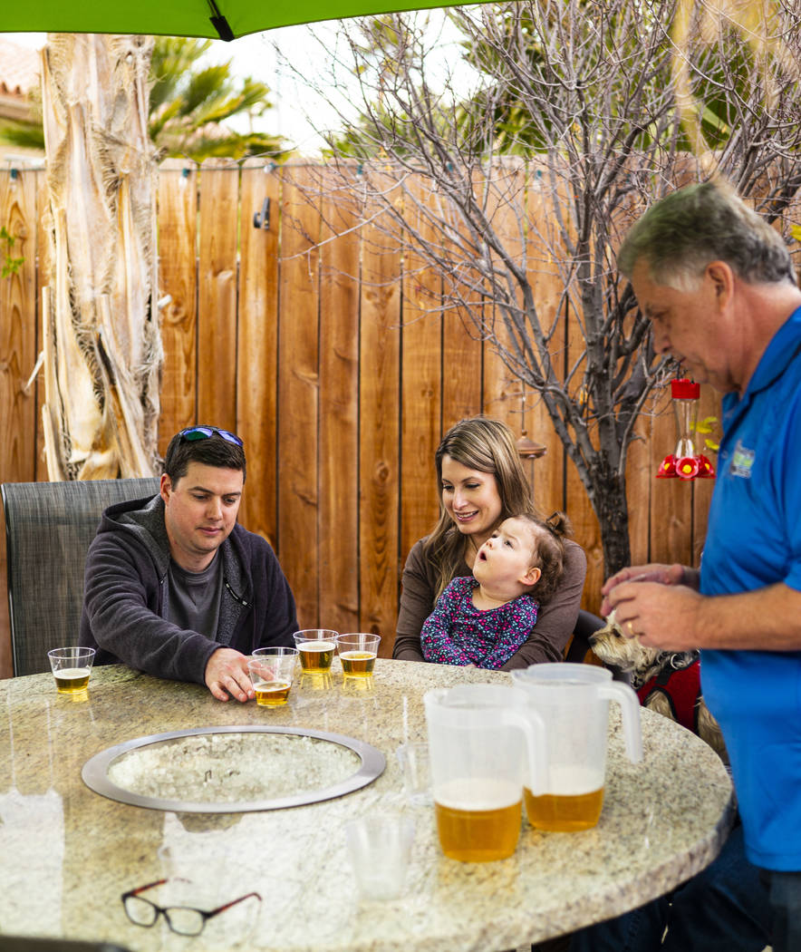 Jason and Lauren Taylor, with daughter Ariana, participate in a beer-tasting exercise led by he ...