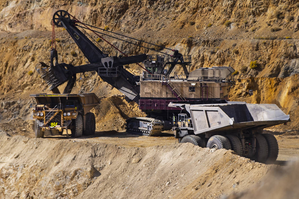 Haul trucks that can carry over 300 tons of material line up by a large excavator at Nevada Gol ...