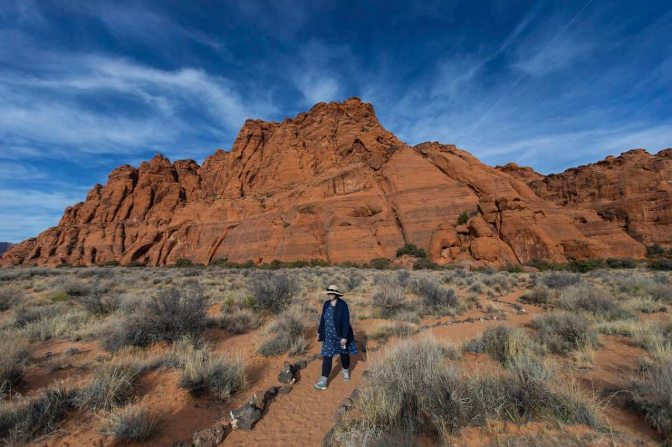A hiker returns from Jenny's Canyon Trail at Snow Canyon State Park near St. George, Utah, wi ...