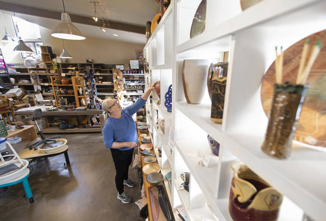 Kathy Barth reaches for a vase at the Zia Pottery Gallery in Kayenta Art Village. (Benjamin Hag ...