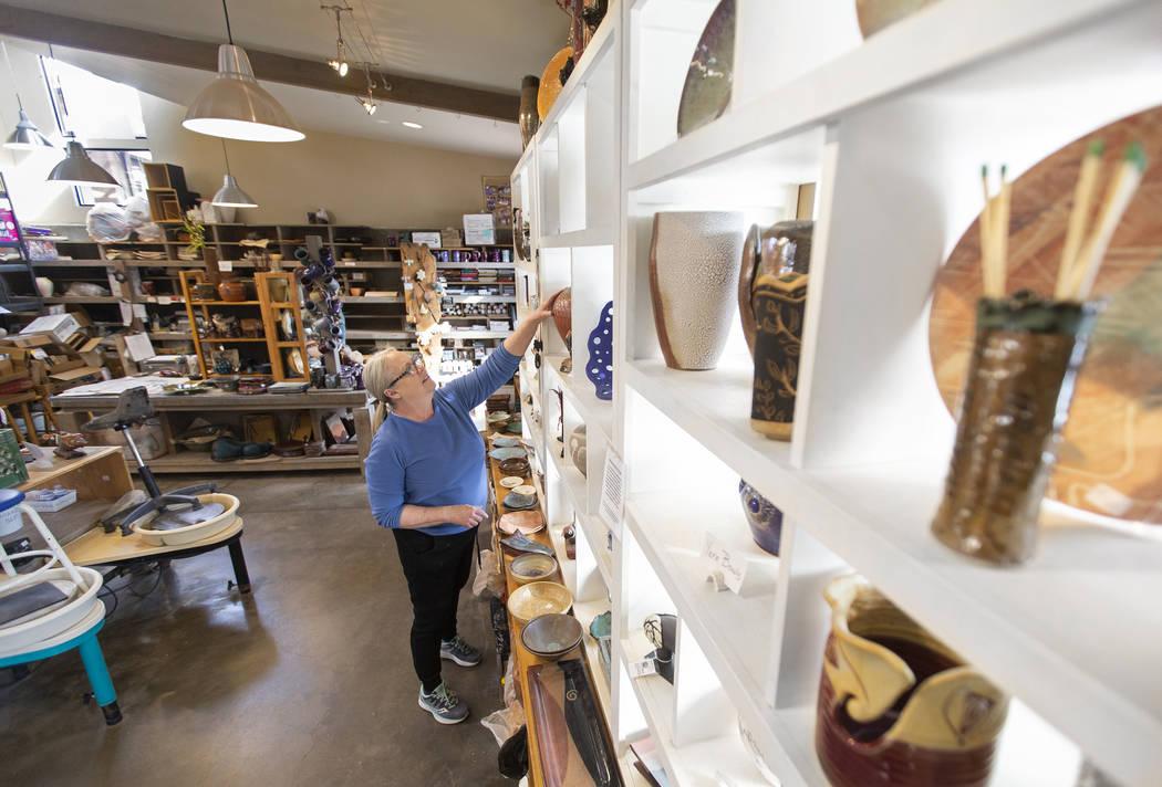Kathy Barth reaches for a vase at the Zia Pottery Gallery in Kayenta Art Village. (Benjamin Hag ...