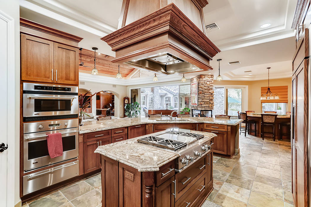 The kitchen features a large center island with granite countertop and gas cooktop. (Berkshire ...