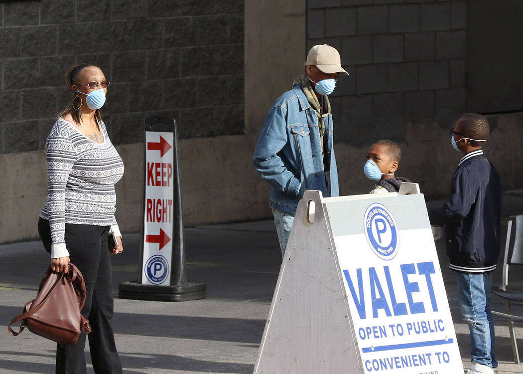 Customers wear protective masks as they wait for their vehicle at Douglas Valet Parking on Lewi ...