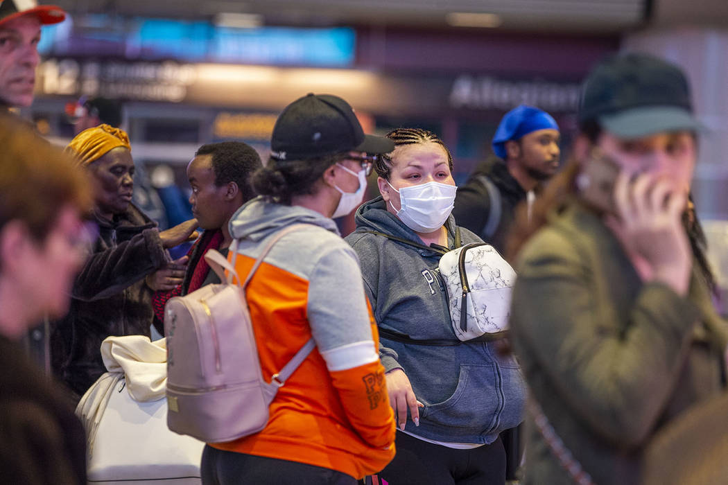 Passengers Sherry Carter, left, and Kimberly Thompson of Virginia wear face masks while awaitin ...