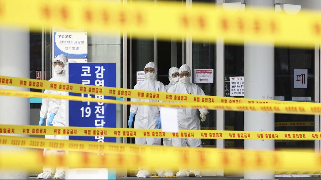 Medical staff wearing protective suits outside a hospital in Daegu, South Korea, Sunday, March ...