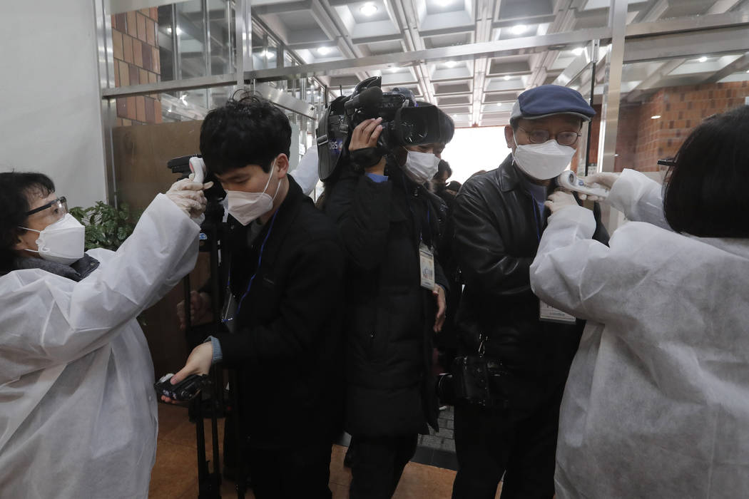 People check the temperature of journalists wearing face masks as they enter the Yoido Full Gos ...