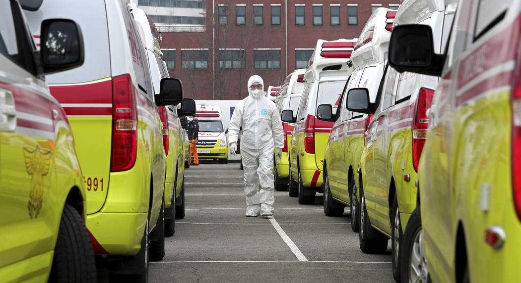 A health worker wearing a protective suit walks between the ambulances to transport patients in ...