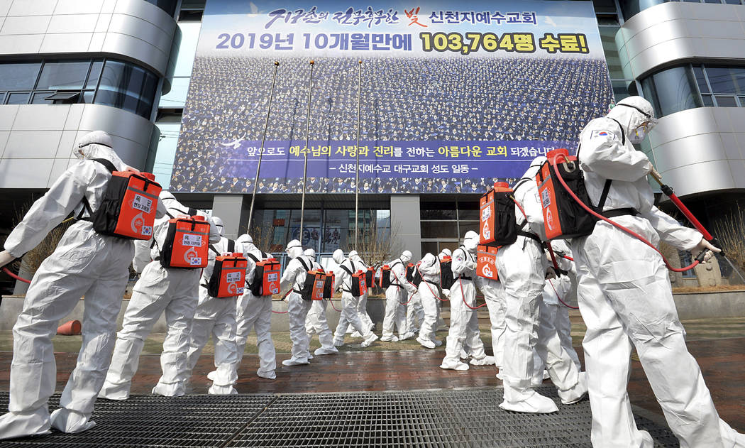 Army soldiers wearing protective suits spray disinfectant to prevent the spread of the coronavi ...