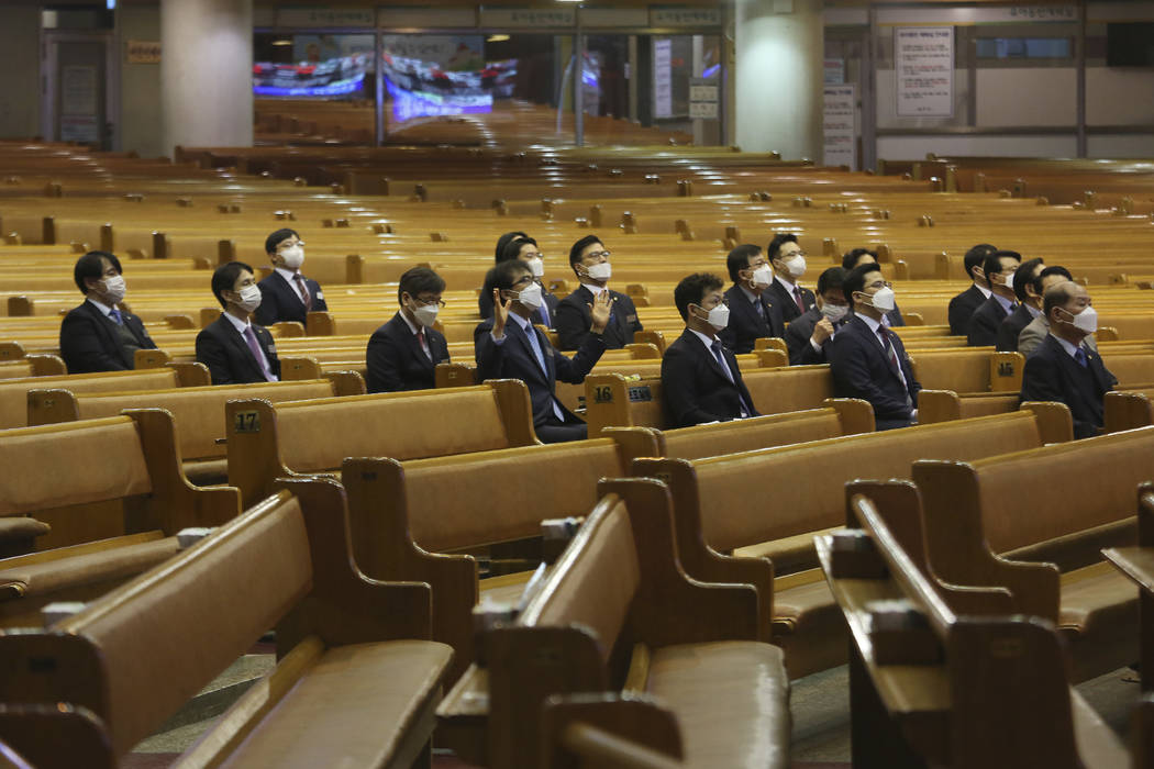 People wearing face masks attend Mass at the Yoido Full Gospel Church in Seoul, South Korea, Su ...
