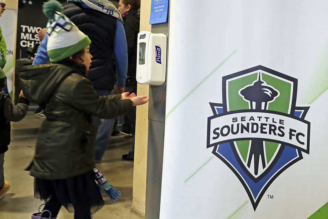 A young fan makes use of a hand-sanitizing station at CenturyLink Field prior to an MLS soccer ...