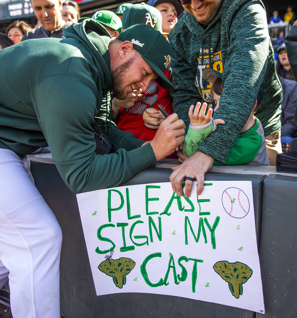 Oakland Athletics pitcher J.B. Wendelken signs the cast of Charleston Kenton, 6, joined by his ...