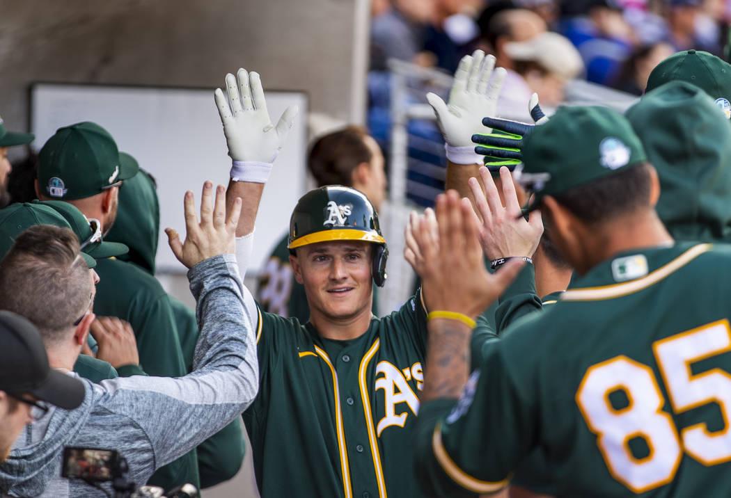 Oakland Athletics infielder Matt Chapman (26) helps celebrate their first run versus the Clevel ...