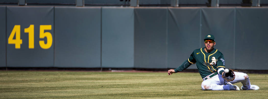 Oakland Athletics outfielder Ramon Laureano (22) makes a sliding catch over the Cleveland India ...