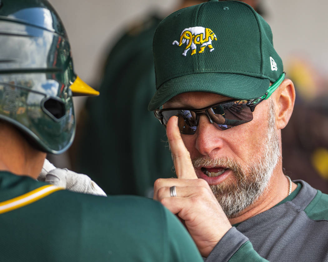 Oakland Athletics quality control coach Mark Kotsay, right, counsels a player in the dugout ver ...