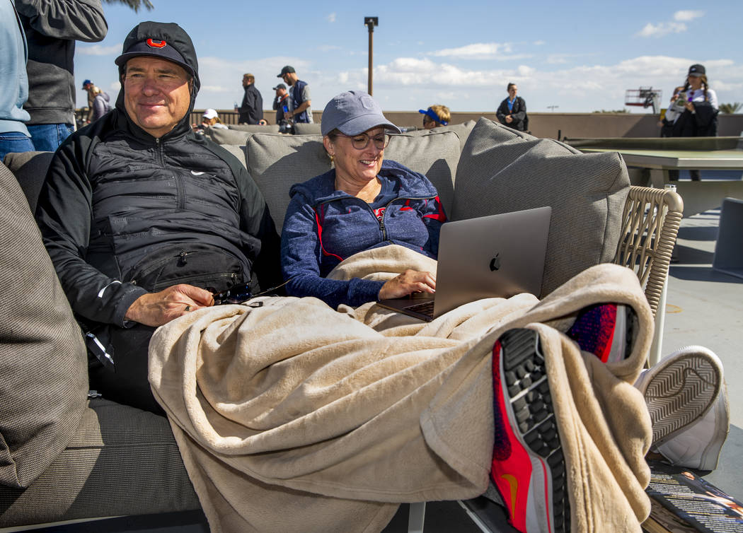 Val, left, and Jenne Hunter of Alpine, Utah, stay warm on a right field couch as the Cleveland ...