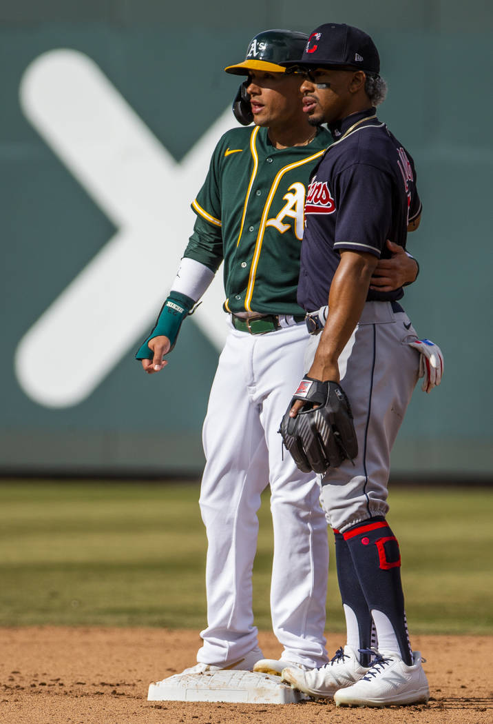 Oakland Athletics runner Ryan Goins (23, left) share a friendly moment with Cleveland Indians i ...