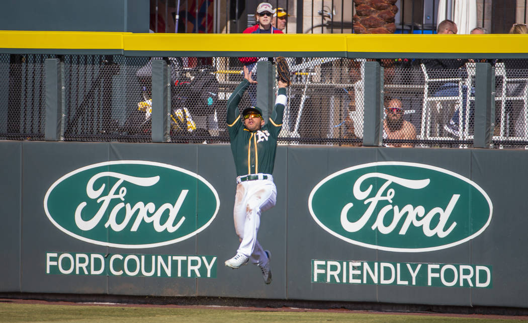 Oakland Athletics outfielder Ramon Laureano (22) makes a jumping catch over the Cleveland India ...