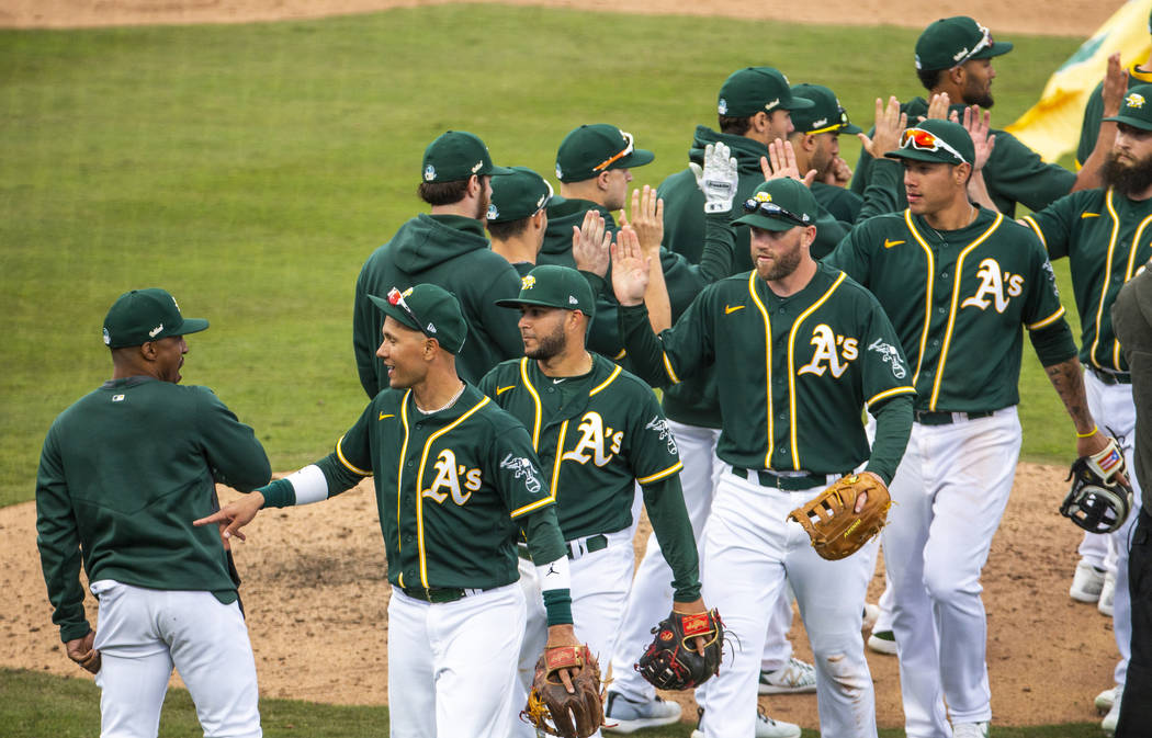 Oakland Athletics players congratulate each other after defeating the Cleveland Indians 8-5 du ...