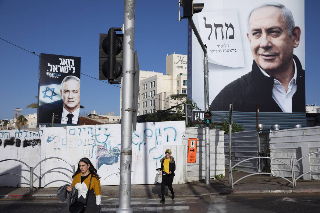 People walk next to election campaign billboards for Likud Party, shows Israeli Prime Minister ...