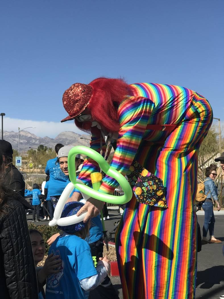 Charlie the Clown makes balloon crowns for children during Walk4Friendship at Bet Yossef Commun ...