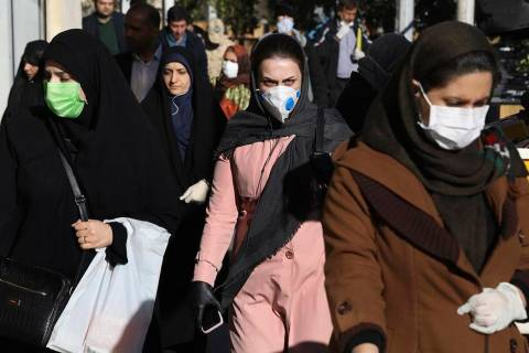 People wearing face masks walk on a sidewalk in downtown Tehran, Iran, Monday, March 2, 2020. A ...