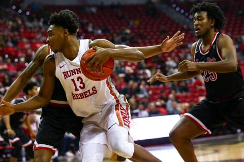 UNLV's Bryce Hamilton (13) drives to the basket past Fresno State's Anthony Holland (25) during ...