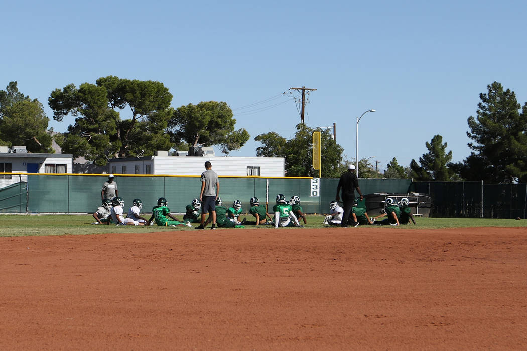 The Rancho High School football team stretches in the outfield of the school's baseball field i ...