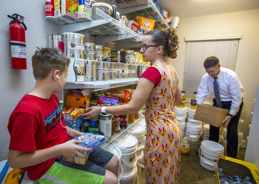Zachary Steed, 11, holds boxes for his mother Holly as she and husband Cory restock some of the ...