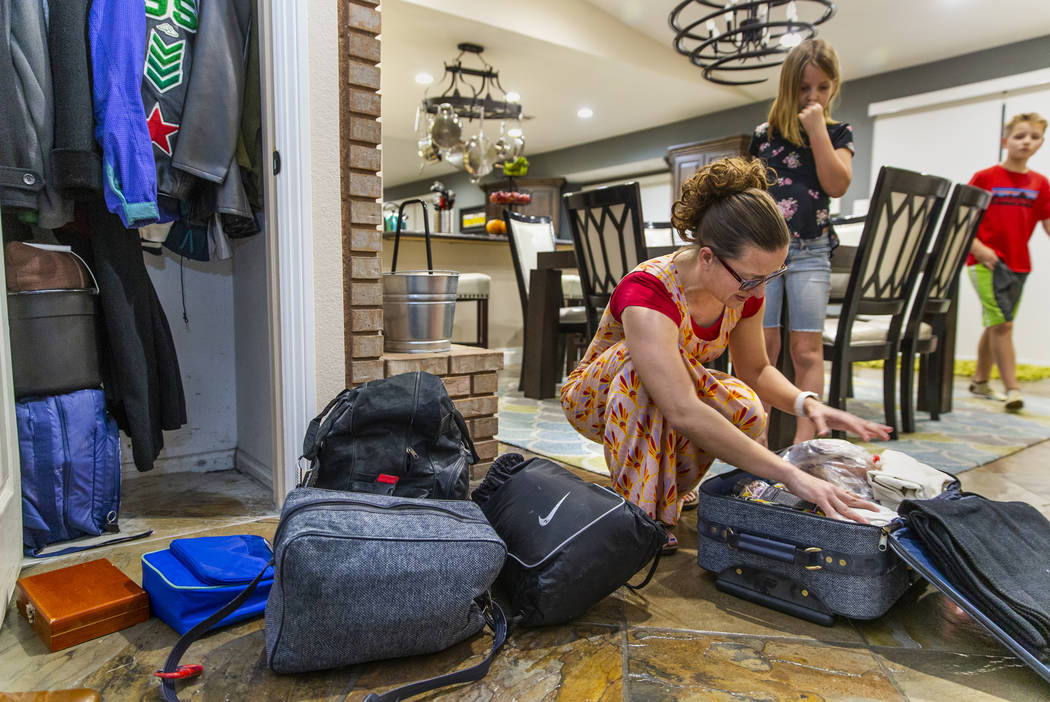 Holly Steed checks on some of the supplies in their 72-hour emergency bags stored in the hall c ...