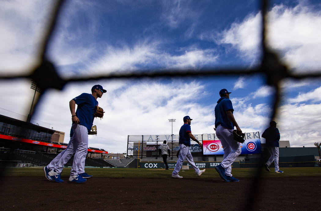 Chicago Cubs players take the field to warm up before a baseball game against the Cincinnati Re ...