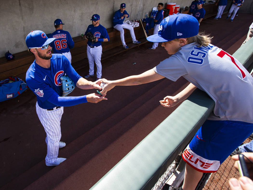 Chicago Cubs' Kris Bryant signs a baseball for Colton Osmulski, 9, of Denver, before the start ...