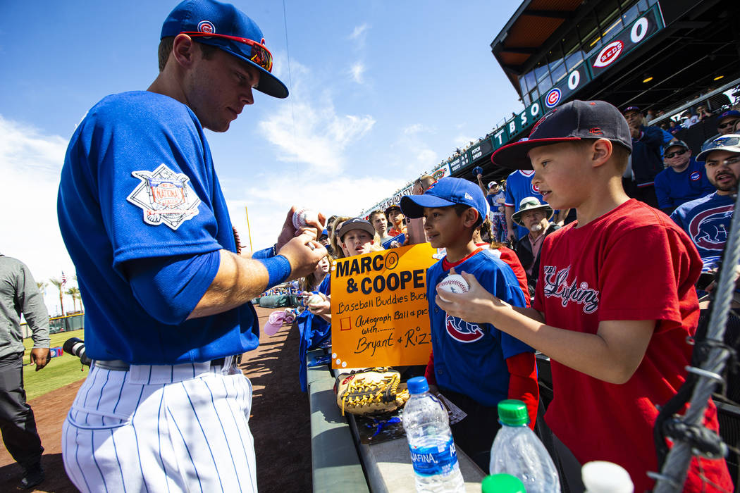 Chicago Cubs' Nico Hoerner signs baseballs for Marco Cooper, 10, center, and Cooper Gunderson, ...