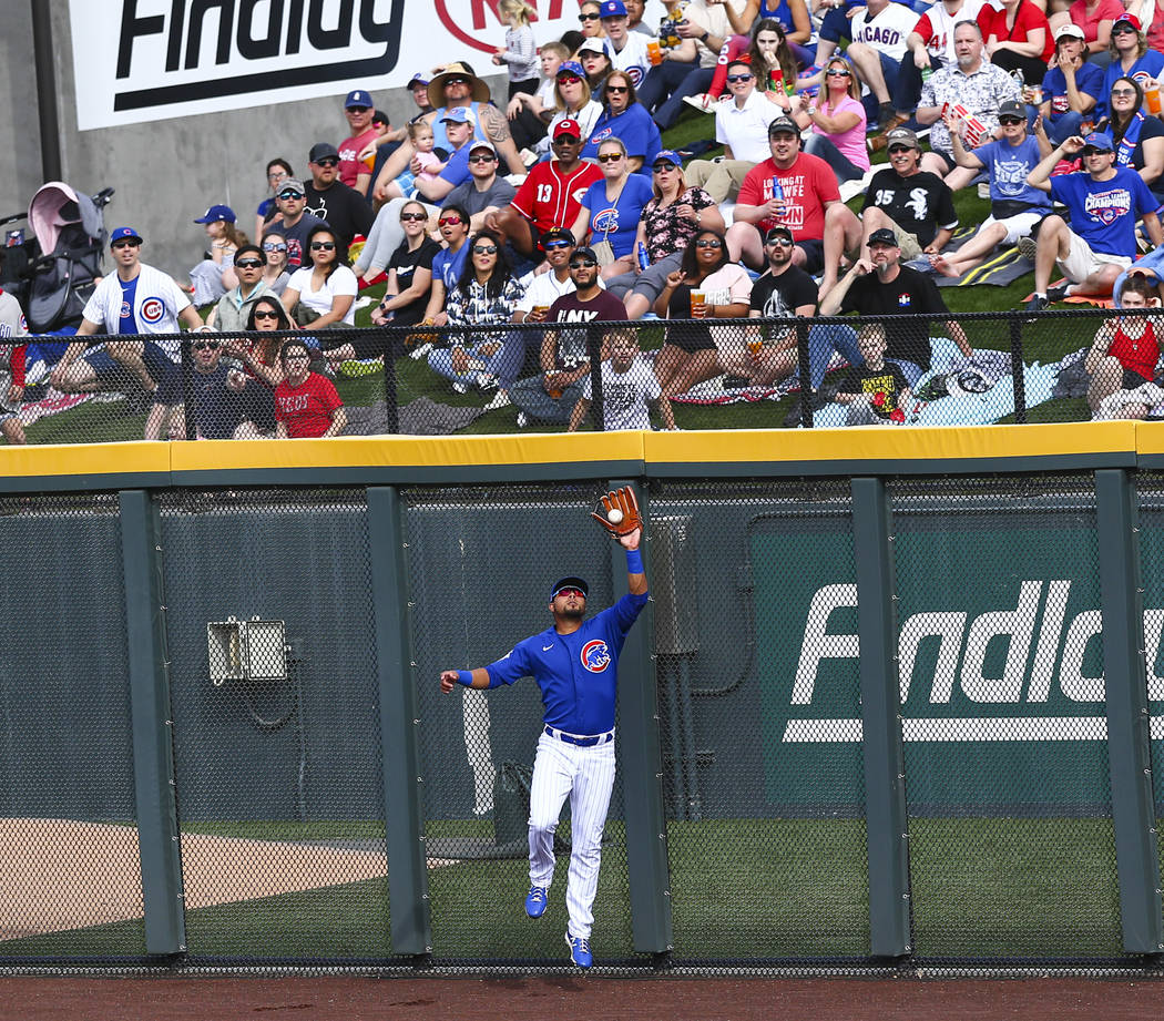 Chicago Cubs' Noel Cuevas catches a fly ball from Cincinnati Reds' Mike Moustakas, not pictured ...