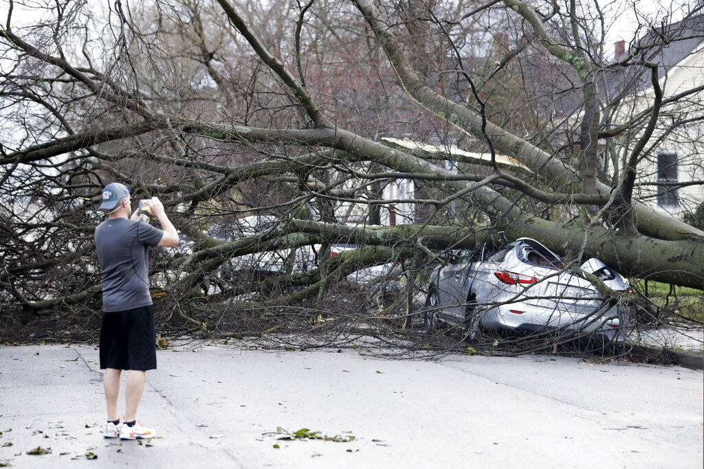 A resident photographs damage after a tornado touched down Tuesday, March 3, 2020, in Nashville ...