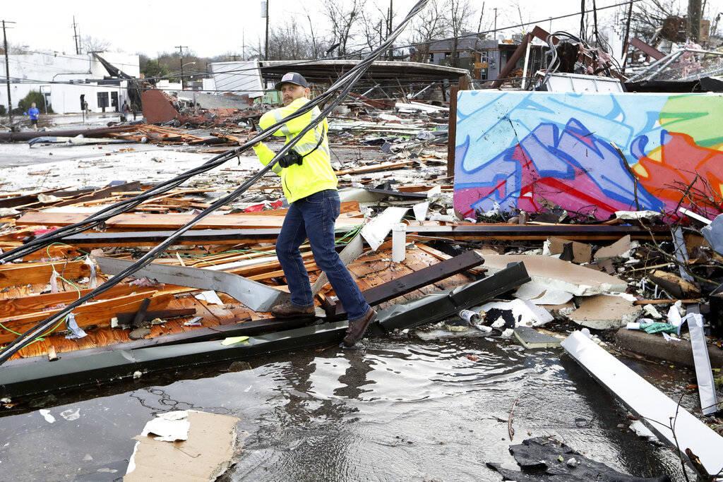 A man makes his way through debris following a deadly tornado Tuesday, March 3, 2020, in Nashvi ...
