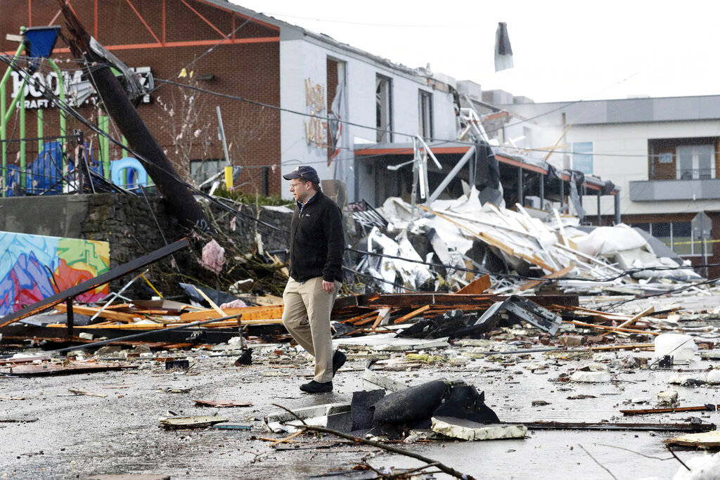 A man walks past storm debris following a deadly tornado Tuesday, March 3, 2020, in Nashville, ...