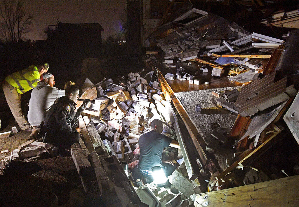 Rescue workers work to free Bill and Shirley Wallace from their home that collapsed and trapped ...