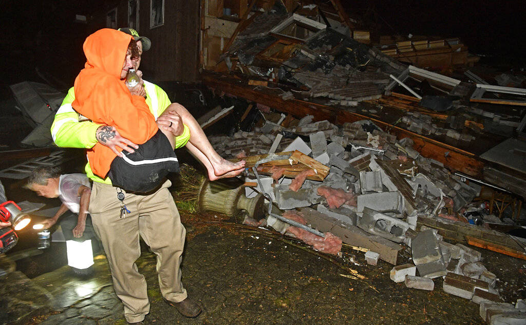 A rescue worker carries Shirley Wallace from her home that collapsed and trapped her under rubb ...