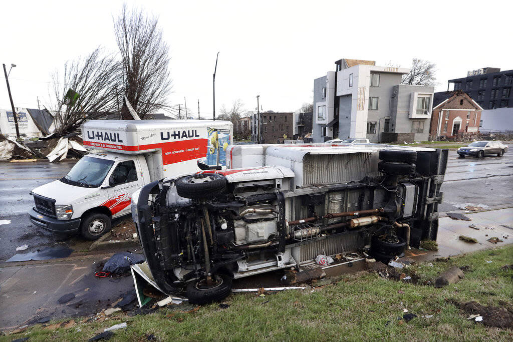 Damaged trucks sit on a sidewalk as well as the street following a deadly tornado, Tuesday, Mar ...