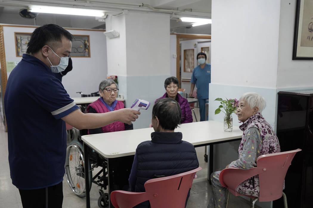 Elderly women receive temperature checks in a nursing home in Hong Kong, Friday, Feb. 14, 2020. ...