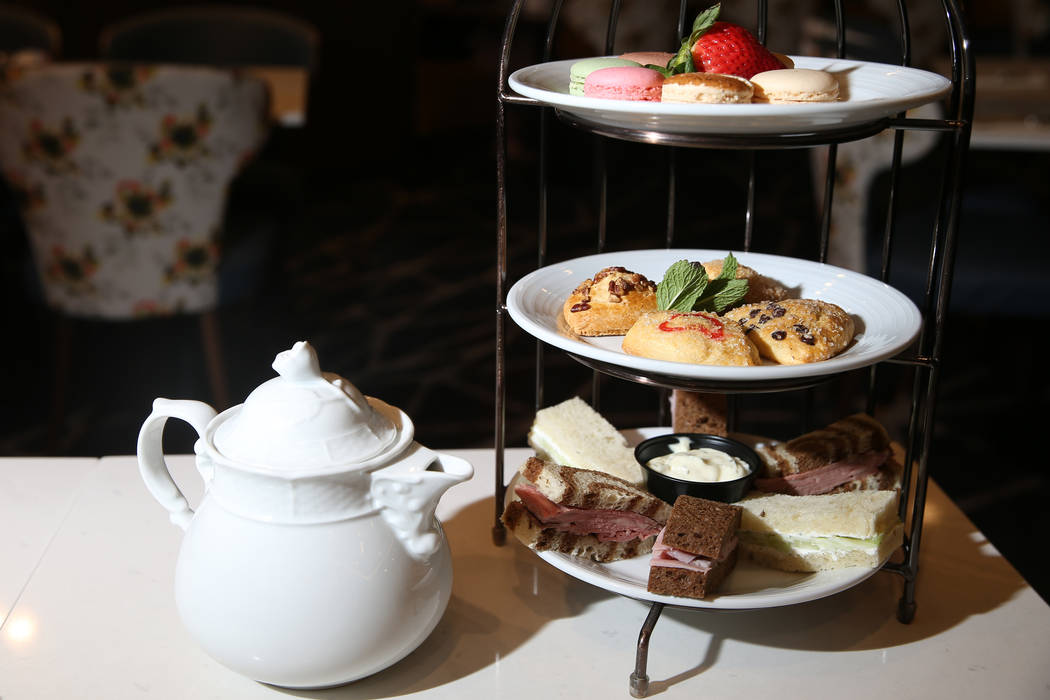 The tea party for two is served with tea, pastries and finger sandwiches with ham, roast beef a ...