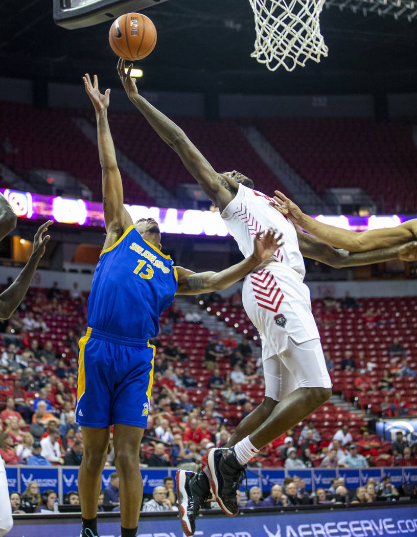 New Mexico Lobos forward Corey Manigault (1, right) touches in a shot over San Jose State Spart ...