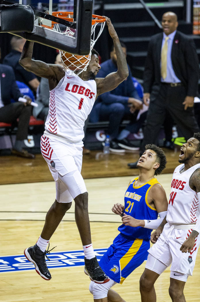New Mexico Lobos forward Corey Manigault (1, above) dunks over San Jose State Spartans guard Ka ...