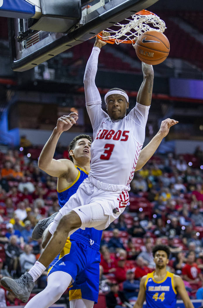 New Mexico Lobos guard Keith McGee (3, right) dunks after beating San Jose State Spartans forwa ...