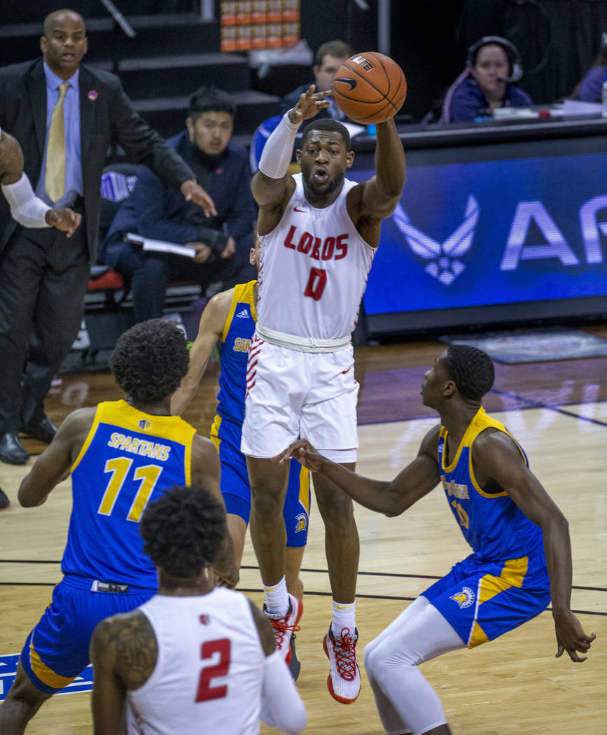 New Mexico Lobos guard Zane Martin (0, above) elevates in triple coverage to get off a pass bet ...