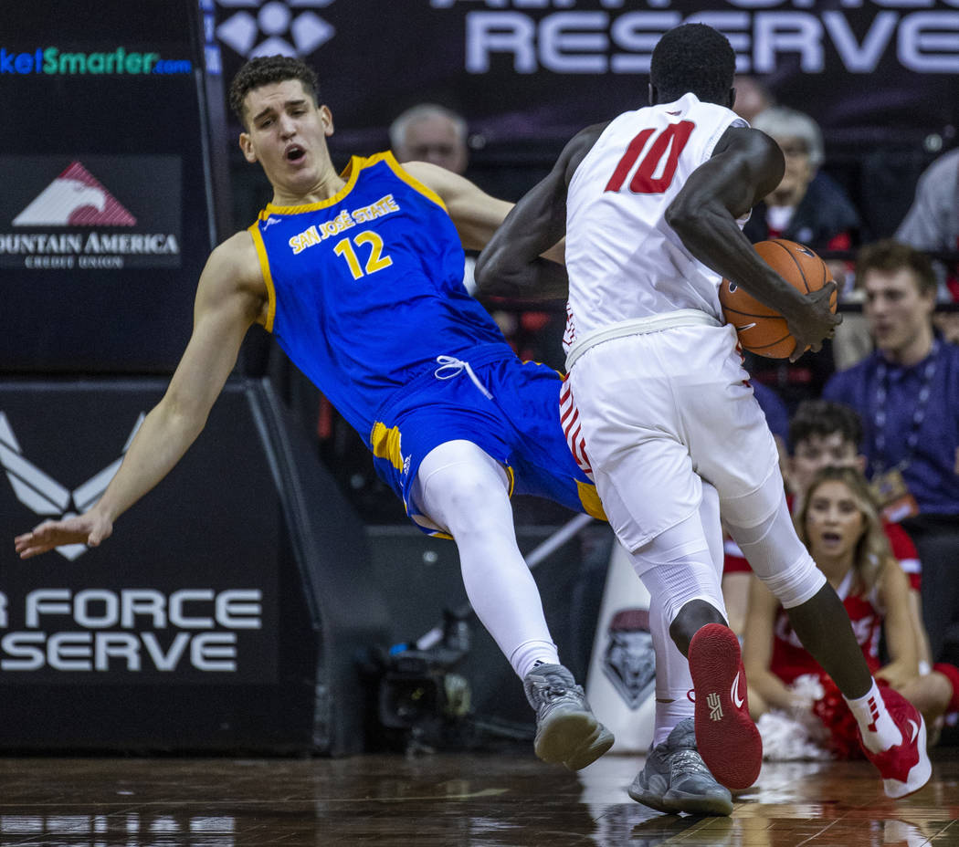 San Jose State Spartans forward Eduardo Lane (12, left) absorbs a charge from New Mexico Lobos ...