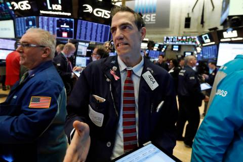 Trader Gregory Rowe, center, works on the floor of the New York Stock Exchange, Thursday, March ...