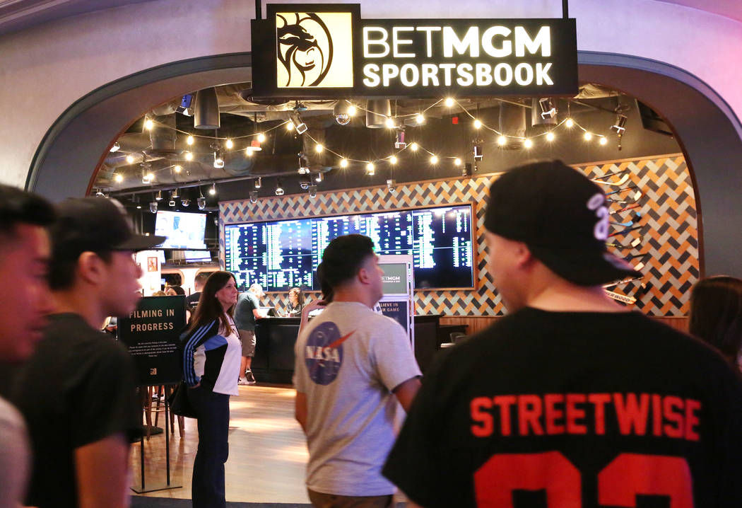 Gusts walk past the new sportsbook at Park MGM on Friday, March. 6, 2020, in Las Vegas. (Bizuay ...