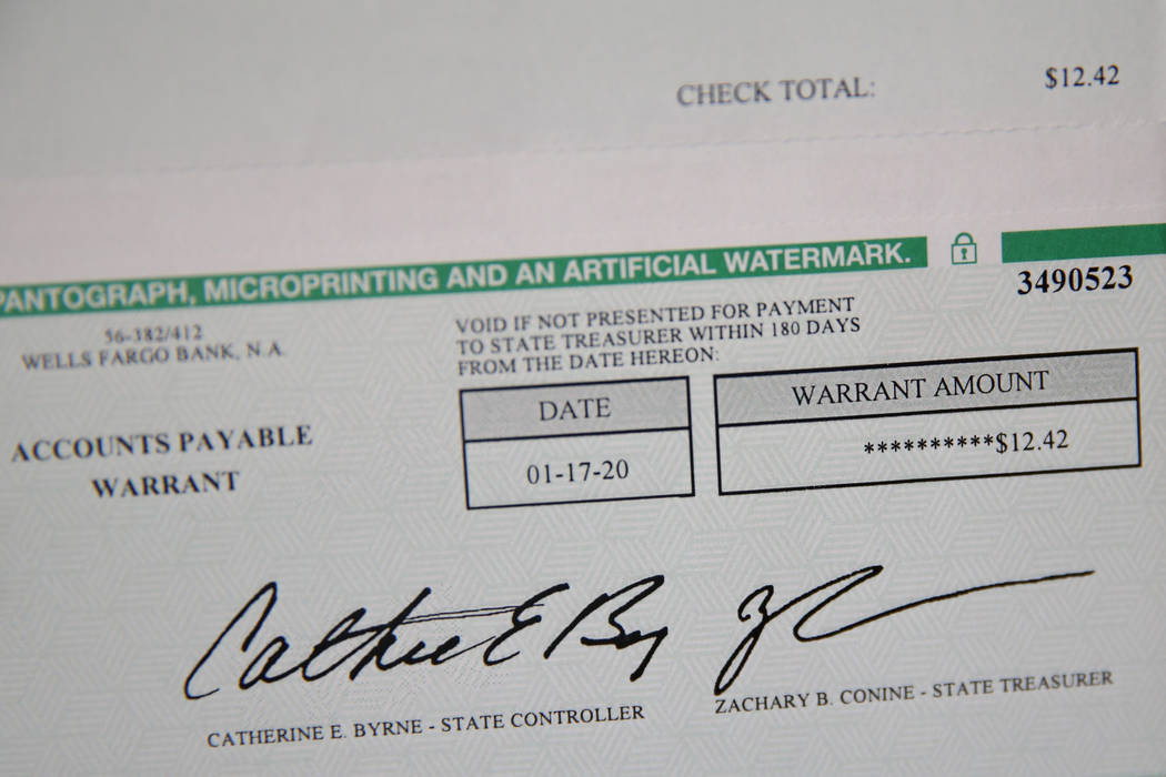 Scott Garner shows a restitution payment he received at his home in Henderson, Saturday, March ...