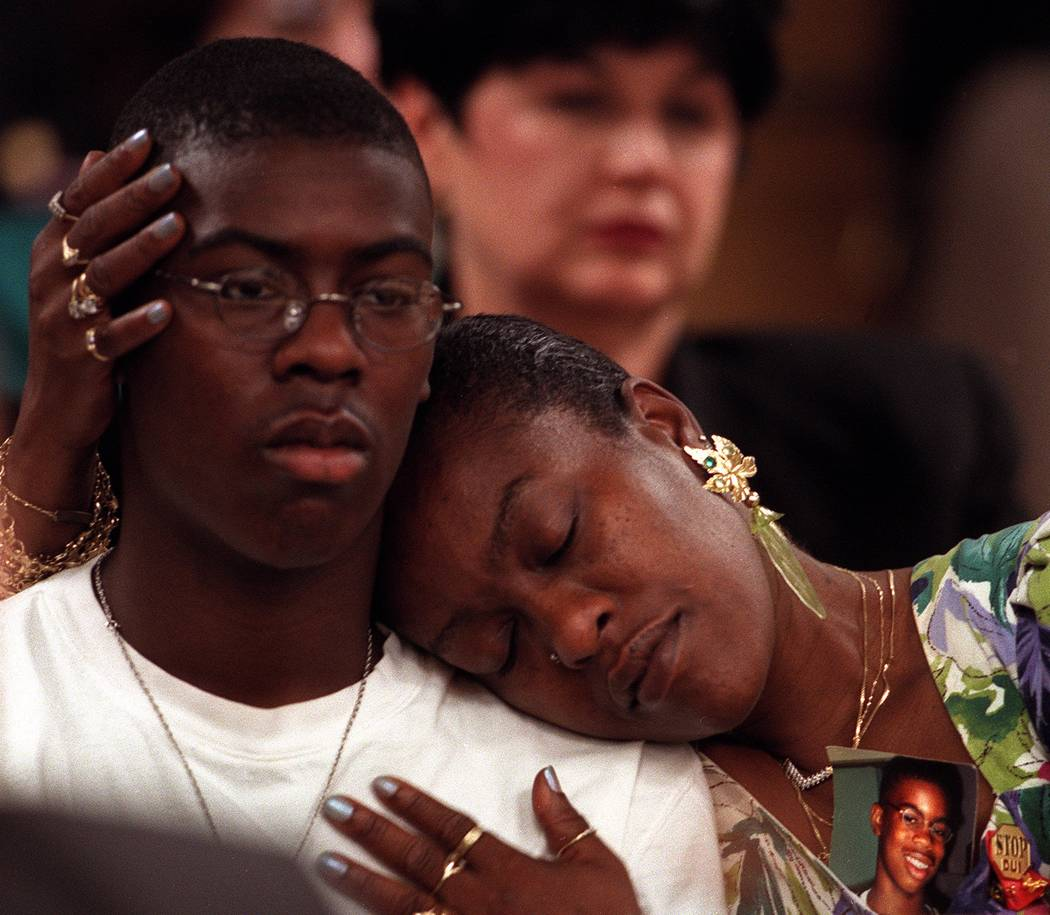 Brigitte Smith embraces her son T.J., 15 with a picture of her dead son Anthony, 14, strapped t ...